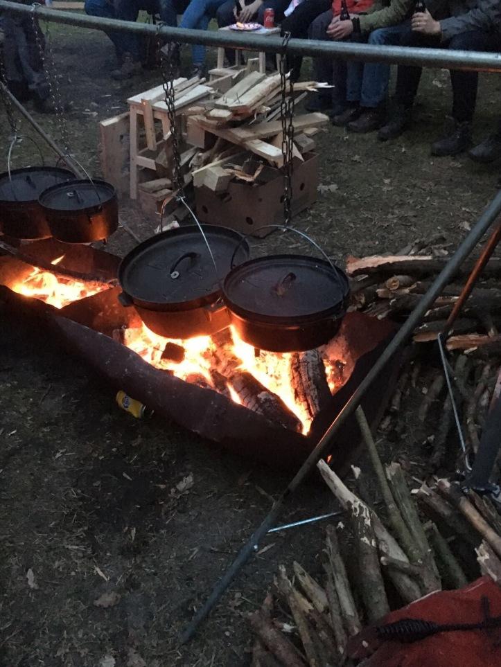 In gietijzeren pannen koken boven houtvuur.